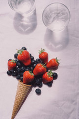 fresh berries on white background, summer tasty dessert fruits and berries, glass of water. Detox, diet concept, summer food, vegetarian, vegan