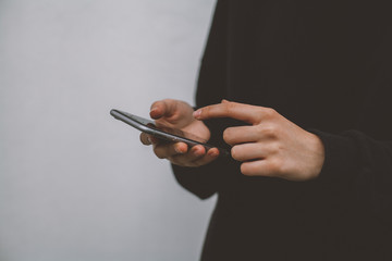 Close up image of young hipster girl using modern smartphone device, female hands holding mobile phone on city street, cropped view of woman browsing internet