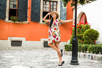 young beautiful girl in summer dress, straw hat. Travels around the European city in the summer. Cheerful, smiling lady. old houses, paving stones, vintage style, old town