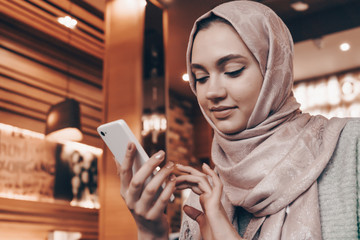 beautiful Arab girl in hijab at a cozy restaurant, writes a message on her smartphone