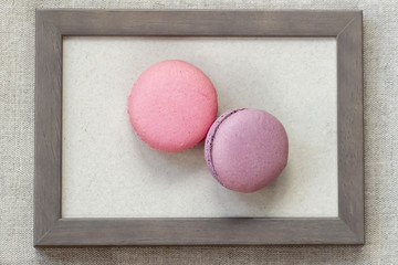 Two fresch macaroons of pink and violet colors in wooden frame, unusual abstract sweet art