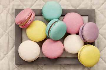 Fresh natural colorful macarons of different tastes in wooden frame on light napkin, top view, unusual abstract sweet art, gourmet gift