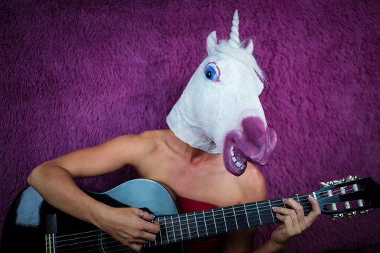 Freaky young woman in comical mask playing the guitar on the purple background. Portrait of unusual lady in red dress with musical instrument. Musical performance.