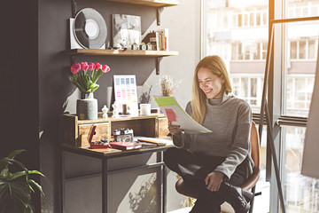 Portrait of laughing girl looking at documents while sitting at table during work in modern showroom. Fashion designer concept