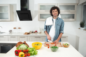 I like cooking. Waist up portrait of happy guy making salad with enjoyment. He is looking at camera and laughing