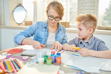 Pretty young tutor in casualwear teaching cute little pupil how to use scissors correctly while making creative present for Fathers Day, interior of modern classroom on background