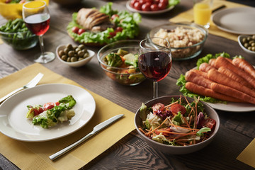 Close up of big plate with veggie salad surrounded by bowls with various healthy cuisines. Glasses of red wine and cutlery are lying nearby