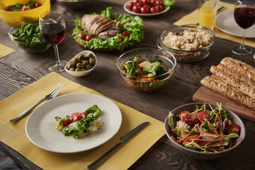 Close up of delicious healthy meal. White plate with salad lying together with vegetables, meat, and other nutritious dishes in different bowls on brown wooden board