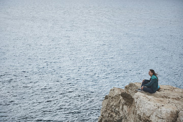 Happy female tourist is enjoying seascape and smiling. She is sitting on rock hill with relaxation. Freedom concept