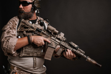 Brutal man in the military desert uniform and body armor stands in a fighting rack and holds his rifle on a black background. The bearded player in the airsoft safety glasses aiming a rifle