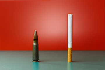 Cigarette and bullet abstract concept . Green and red background as a symbol of life and death