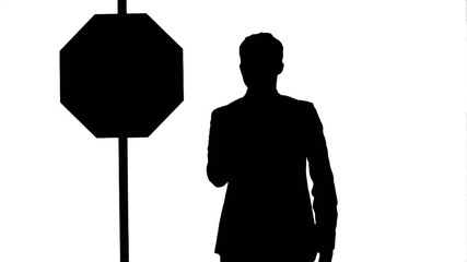 Silhouette Businessman standing near a stop sign on laptop.