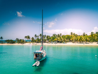 isolated sailboat anchoring in front of a white sand beach on Caribbean island - Mayreau - St Vincent and the Grenadines