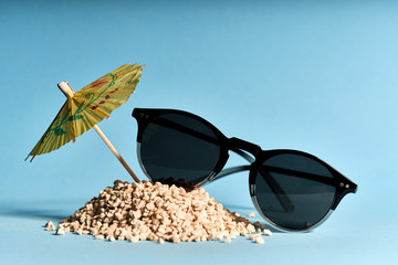 cocktail umbrella, sand and sunglasses