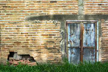 Zinc gate with old bricks wall and grass background