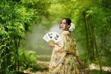 Asian girl wearing a kimono carrying a blow