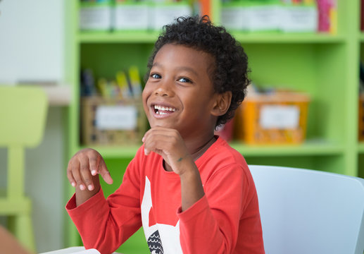 African American ethnicity kid smiling at library in kindergarten preschool classroom.happy emotion.education concept.