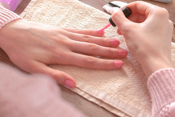 Woman puts second coat of pink shellac on her nails. Close-up hands.