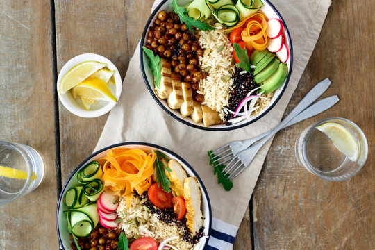 Top view two buddha bowl lemon water Clean balanced healthy food concept Chicken grilled steak rice spicy chickpeas black white quinoa avocado carrot zucchini radish tomatoes wooden table