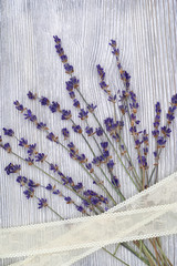 Branch of Lavender on wooden textural surface with band. Copy space.  Natural background with blue flowers of lavender. Top view.