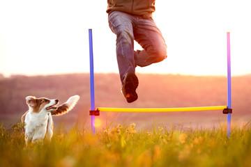 Mann springt über eine Hürde, Welpe oder kleiner Hund läuft nebendran