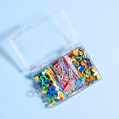A set of stationery made of multi-colored buttons and paper clips in a box on