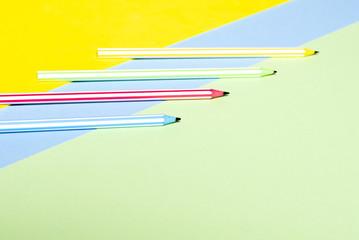 Multi-colored striped beautiful pencils in tri-color background