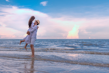 Happy young couple holding each other and laughing with enjoying together on the summer beach, romantic couple spending time concept.