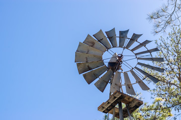 Old rusty windmill in sun with blue sky for copy text