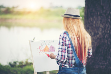 Beautiful girl draws a picture in the park