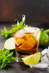 Summer cooling alcoholic beverage from cola, whiskey, lime and liqueur in glass on dark concrete old background.