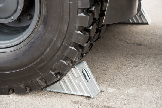 Metallic gray wheel chocks under the big truck wheels