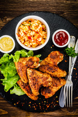 Chicken wings with French fries on wooden background