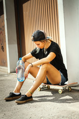 girl is sitting on a skateboard and is resting holding water in hand on a summer day