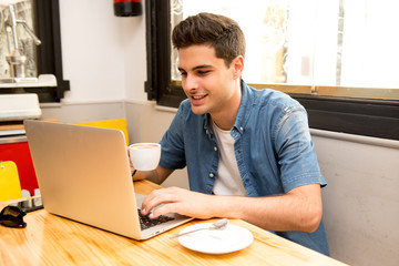 young student man working and studying on computer in coffee shop