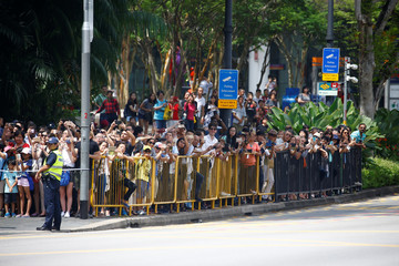 People wait to see U.S. President Donald Trump's motorcade outside the Istana, Singapore