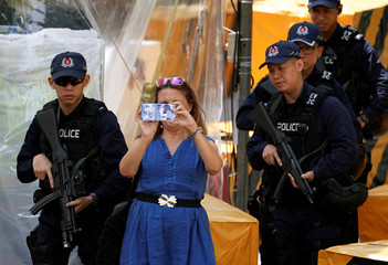 A woman takes photos next to policemen standing guard outside St Regis hotel, in Singapore