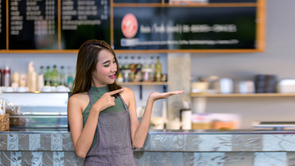 Attractive young Asian beautiful Caucasian barista  in coffee shop counter.