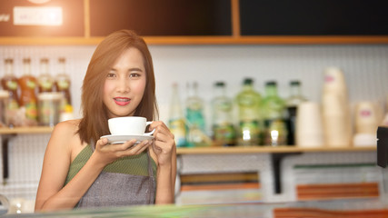 Attractive beautiful Asian barista in apron smiling at camera in coffee shop counter.