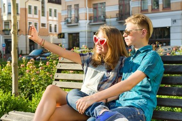 Teenage friends girl and boy sitting on the bench in the city, talking, looking in the phone, doing selfie photo