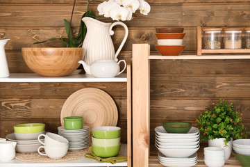 Kitchen shelving with dishes on wooden wall background