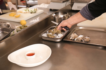 Male chef opening fresh oyster in restaurant kitchen