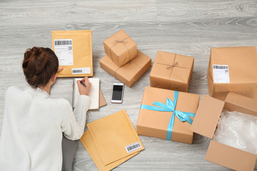 Woman preparing parcels for shipment to customer on floor