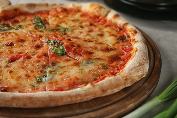 Tasty pizza on board, closeup. Fresh from oven