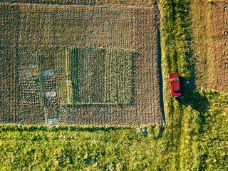 Wall Mural - Aerial view of amid fields with red car on it