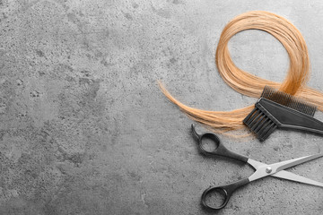 Flat lay composition with hairdresser's tools and strand of blonde hair on grey background