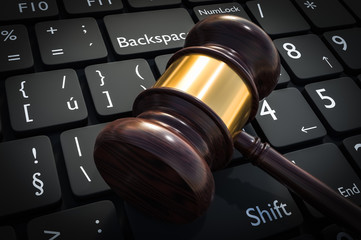 Wooden gavel and keyboard - justice and law concept