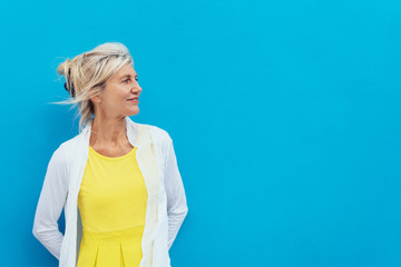 Relaxed confident blond woman against a blue wall