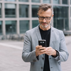 Mature metro man texting on phone in urban scene