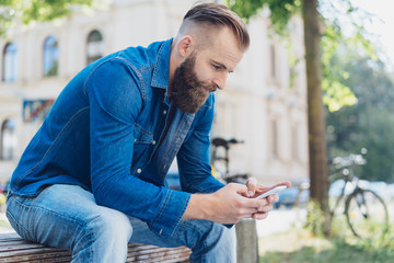Casual man sitting on an urban bench texting